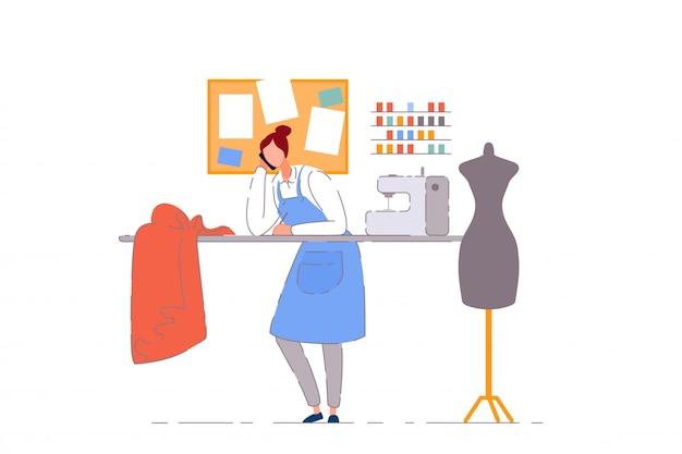 Dueño de negocio de sastrería. modista mujer persona que trabaja en el taller de costura artesanal. sastre costurera dueño de negocio con máquina de coser, maniquí y tela en taller