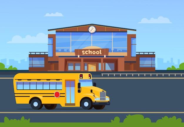 Edificio escolar. exterior de la universidad con autobús amarillo.