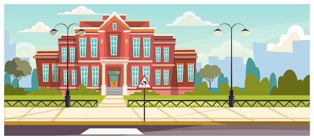 Edificio escolar con valla pequeña alrededor.
