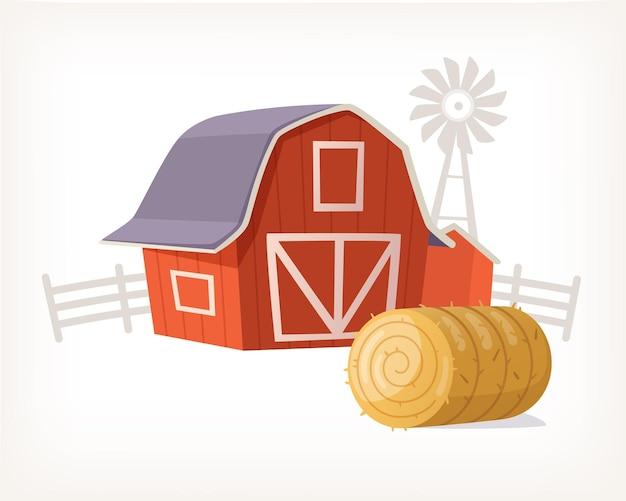 Edificio de granero de granja de madera roja clásica con veleta en el molino de viento superior y rollo de heno cerca de él