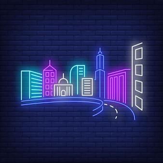 Edificios de la ciudad y letrero de neón de carretera.