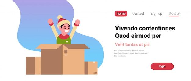 Elf santa claus helper levantó las manos dentro de la caja de papel en navidad