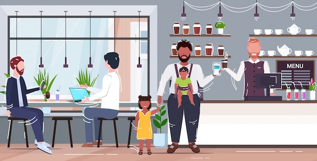 Ella con su pequeño hijo y su hija en el mostrador de la cafetería usando la aplicación móvil que paga el concepto de pago en línea de café familia feliz divirtiéndose moderna cafetería interior horizontal de longitud completa