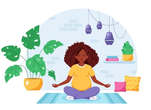 Embarazada afroamericana meditando en posición de loto en interior acogedor