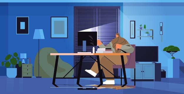 Empresaria árabe con exceso de trabajo sentada en el lugar de trabajo mujer de negocios autónoma mirando la pantalla de la computadora en la noche oscura oficina en casa horizontal ilustración vectorial de longitud completa