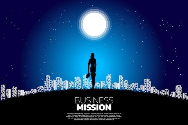 Empresaria de pie en la luna a la luz de la ciudad.