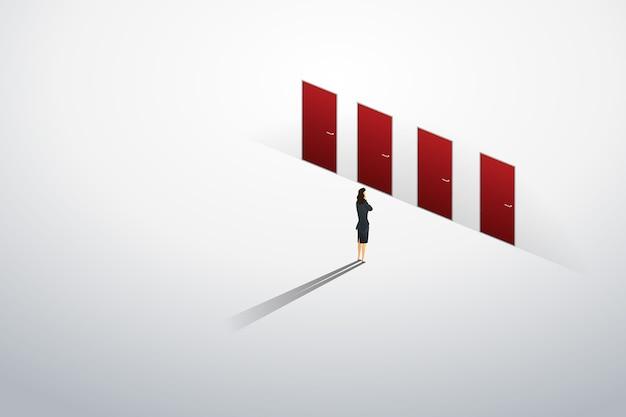 Empresaria de pie pensando en la puerta roja cuatro de elección en el camino de la pared al éxito de la meta.