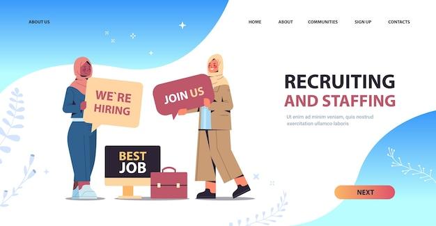 Empresarias árabes gerentes de recursos humanos que sostienen que estamos contratando únase a nosotros carteles vacante de recursos humanos concepto de recursos humanos de reclutamiento abierto ilustración de vector de espacio de copia horizontal de longitud completa