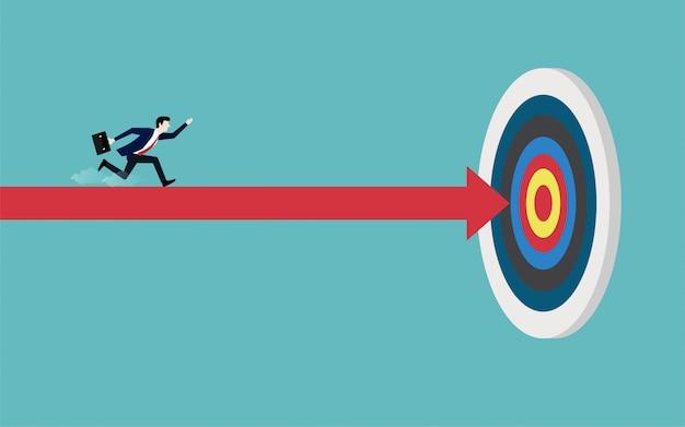 Empresario corriendo sobre una flecha roja apuntando al objetivo