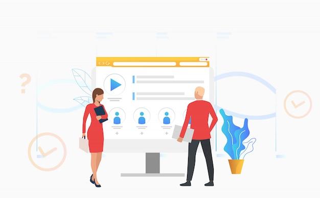 Empresario y empresaria mirando el monitor de la computadora