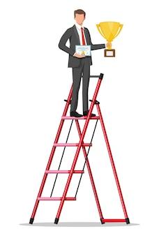 El empresario en la escalera sosteniendo el trofeo, mostrando el certificado de premio celebra su victoria.