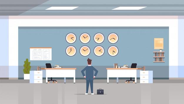 Empresario mirando en la pared con relojes de diferentes ciudades concepto de plazo de gestión del tiempo moderno espacio de trabajo oficina interior horizontal vista posterior personaje masculino de cuerpo entero