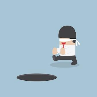 Empresario con los ojos vendados caminando en el agujero