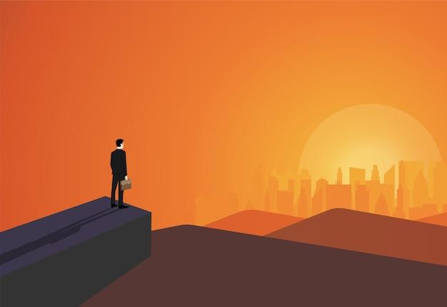Empresario parado en acantilado mira el éxito en la ciudad