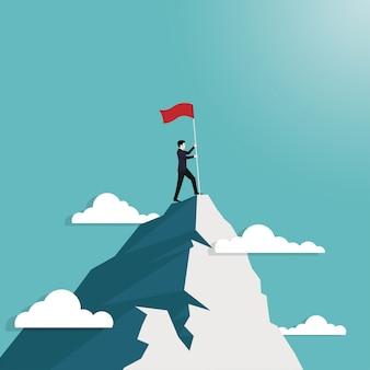 Empresario de pie espera bandera conquistando la cima de la montaña