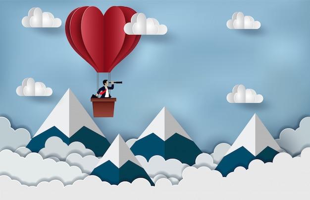 Empresario de pie en el globo aerostático rojo sosteniendo binocular flotando en el cielo