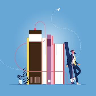 Empresario de pie junto a la pila de libros con auriculares y escucharlos en línea