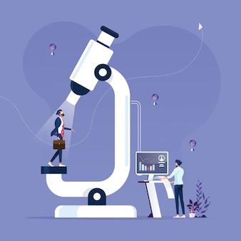 Empresario de pie bajo un microscopio