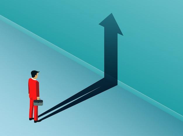 Empresario que está parado buscando el objetivo de éxito con la sombra de una flecha
