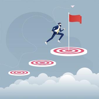 Empresario saltando de una meta pequeña a una meta grande