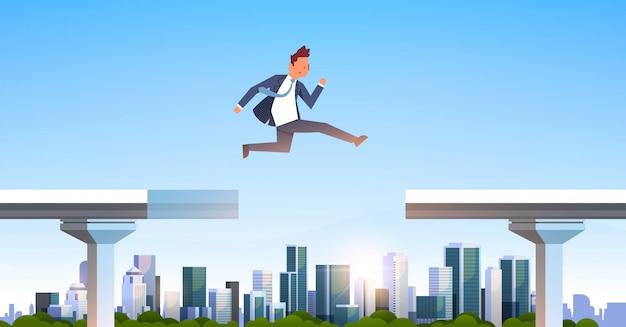 Empresario saltando sobre brecha