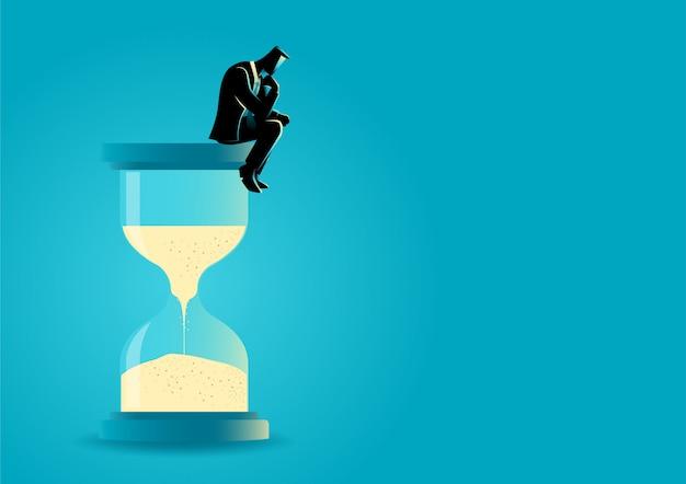 Empresario sentado y pensando en reloj de arena