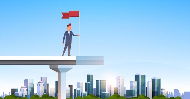 Empresario sosteniendo bandera roja borde permanente puente inacabado