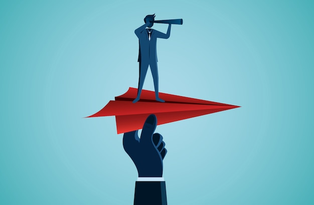 Empresario sosteniendo binoculares en un avión de papel rojo