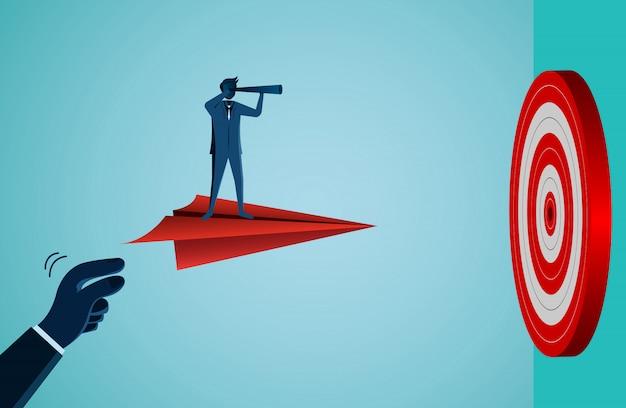 Empresario sosteniendo binoculares en un avión de papel volando hacia el objetivo
