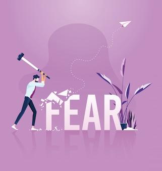 Empresario sosteniendo el martillo golpeando la palabra miedo