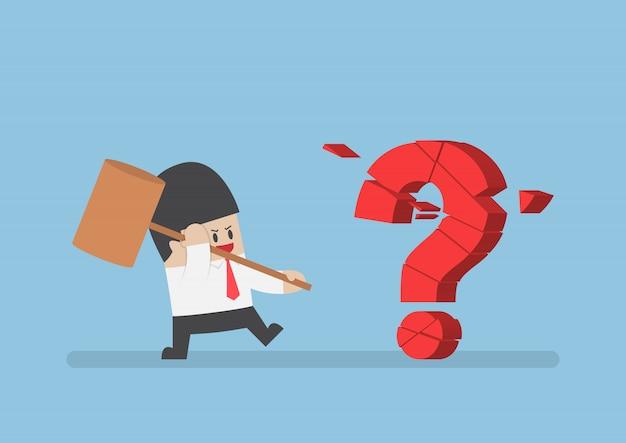 Empresario sosteniendo martillo rompiendo el signo de interrogación rojo