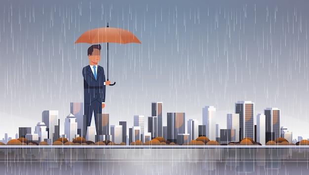 Empresario sosteniendo paraguas en tormenta