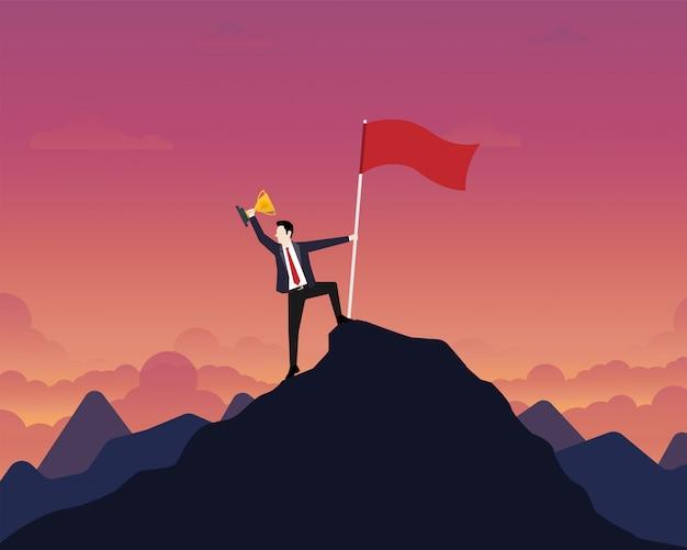 Empresario sosteniendo un trofeo de oro con bandera de éxito en la cima de la montaña