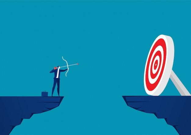 Empresario superior montaña con arco y flecha mira objetivos.