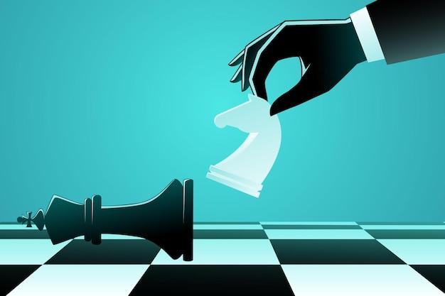 Empresario usando ajedrez caballero caballo para patear un rey de ajedrez