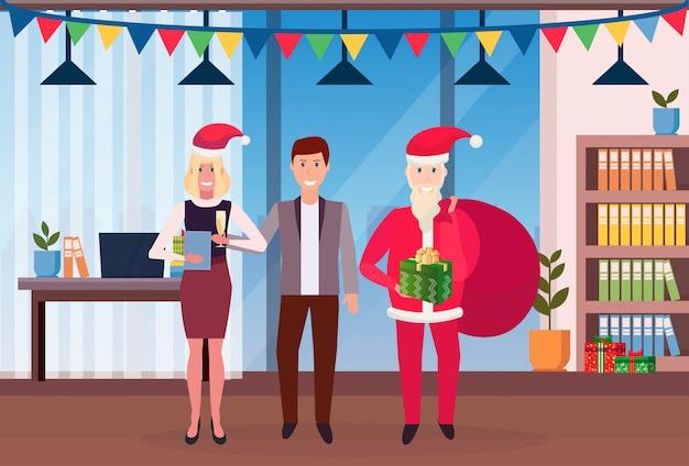 Empresarios celebrando la navidad en la oficina con santa claus