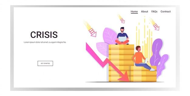 Los empresarios estresados sentados en la pila de monedas usando una computadora portátil cayendo flecha crisis financiera fracaso presupuesto colapso bancarrota concepto copia espacio horizontal