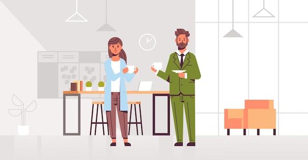 Empresarios pareja bebiendo capuchino hombre de negocios mujer discutiendo durante la reunión coffee break moderno salón interior de la oficina