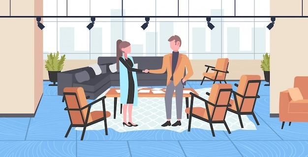 Empresarios pareja estrecharme la mano hombre de negocios mujer apretón de manos acuerdo asociación concepto creativo gabinete moderno oficina interior horizontal longitud completa