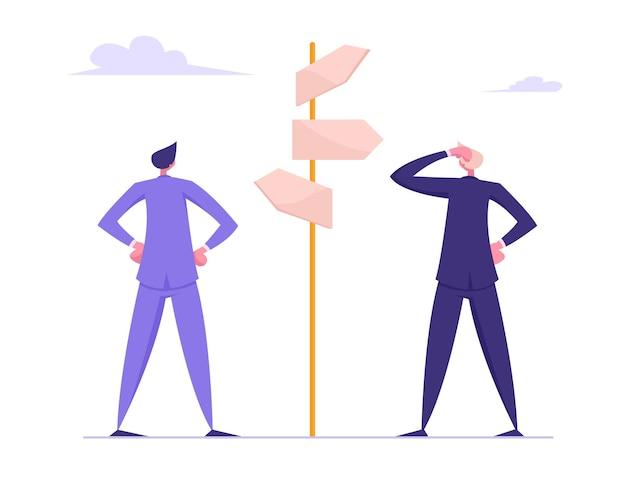 Empresarios de pie en la encrucijada y mirando señales direccionales