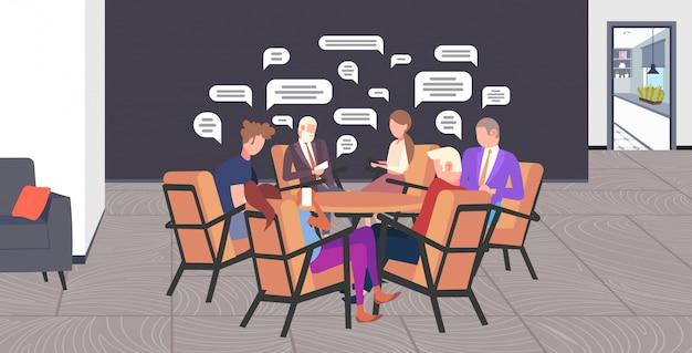 Empresarios sentados en la mesa redonda charlando durante la reunión de redes sociales chat burbuja concepto de comunicación