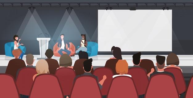 Empresarios sentados en pufs dando discurso en conferencia