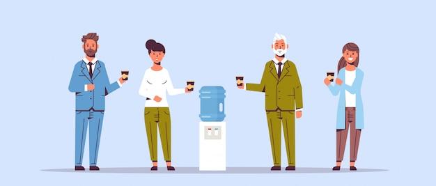 Empresarios trabajadores de oficina hablando y bebiendo agua mientras están parados cerca de empleados más frescos que tienen descanso