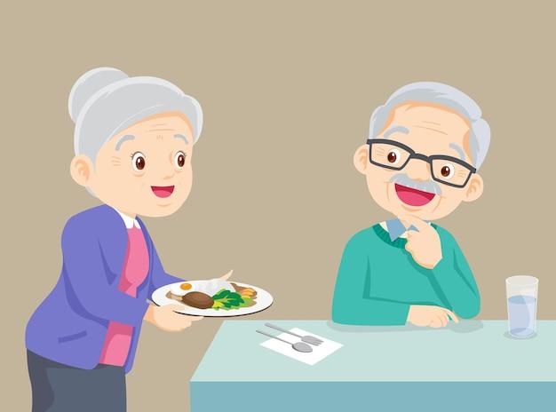 Encantadora abuela sirviendo comida al abuelo