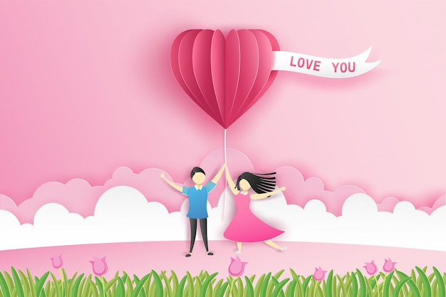 Encantadora pareja en la pradera con corazón de origami globo rosa y flores en el día de san valentín con el texto love you.