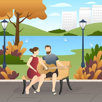 Encantadora pareja sentada en el banco y tocando la guitarra en el parque.