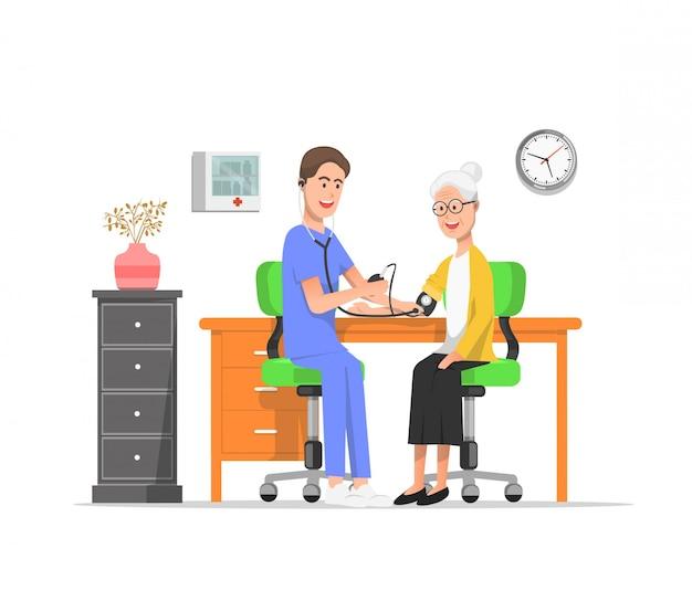 Una enfermera controlando la presión arterial de una anciana.