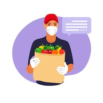 Entrega de mercadería durante la prevención del coronovirus, covid-19. mensajero en una mascarilla con bolsa de papel con frutas y verduras en sus manos. vector ilustración plana.