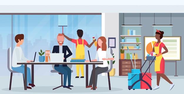 Equipo de conserjes limpiadores afroamericanos en uniforme trabajando juntos concepto de servicio de limpieza centro de trabajo creativo moderno interior de oficina plano horizontal de longitud completa