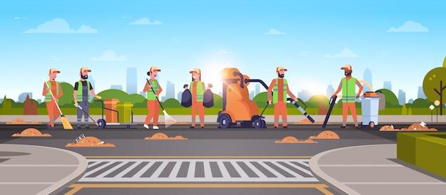 Equipo de conserjes recolectando basura en limpiadores de carreteras usando aspiradora